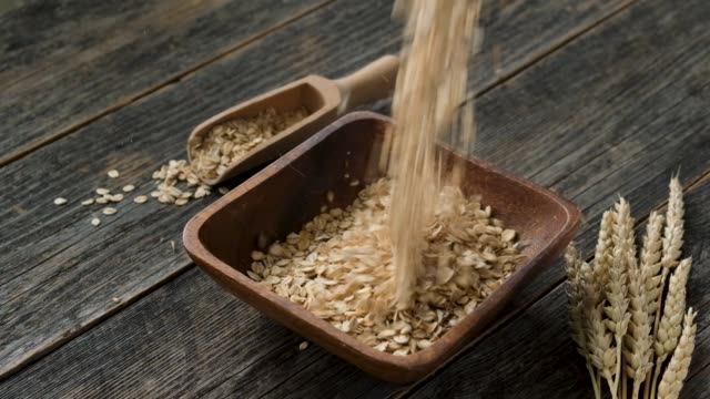 slow motion of oat flakes fall in bowl - oatmeal stock videos & royalty-free footage