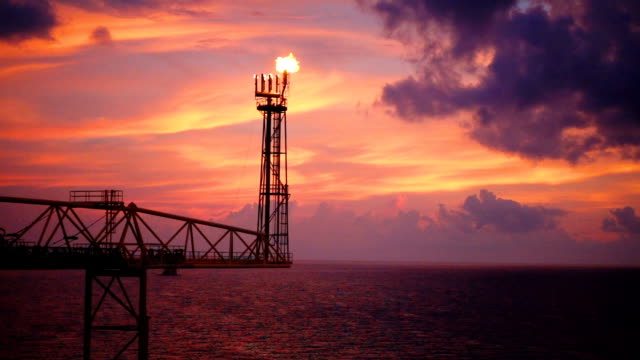 vídeos de stock e filmes b-roll de slow motion of oil and gas platform with flare burning bridge with sun rise and beautiful clouds in the morning for oil and gas industry concept. - fábrica petroquímica