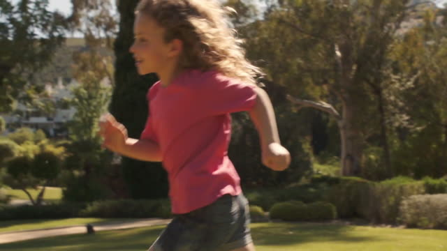 slow motion of one child running round camera in park. - side view stock videos & royalty-free footage