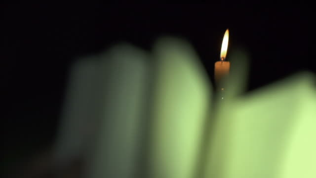 slow motion of opening book pages under candle light - candlelight stock-videos und b-roll-filmmaterial