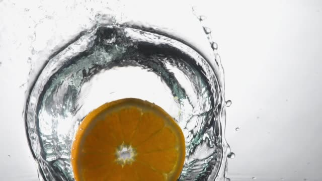 slow motion of orange drop into water and splashing. - refreshment stock videos & royalty-free footage