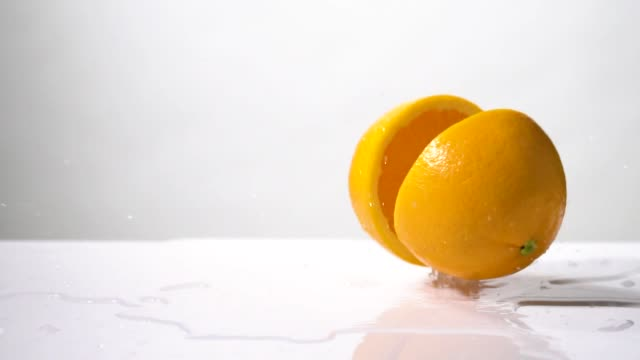 vídeos de stock e filmes b-roll de slow motion of orange slice drop and splashing - laranja