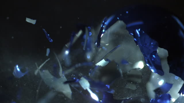 Slow motion of ornament exploding from being shot with air gun.