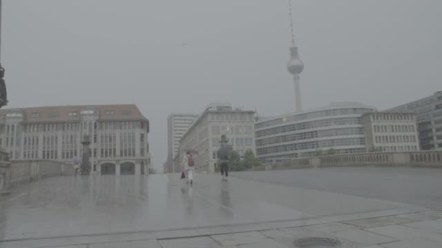 Slow motion of pedestrians using umbrellas in the rain in Berlin Germany on Wednesday July 26 Background of Fernsehturm television tower