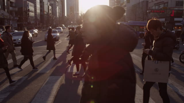 Slow motion of people crossing a road at sunset