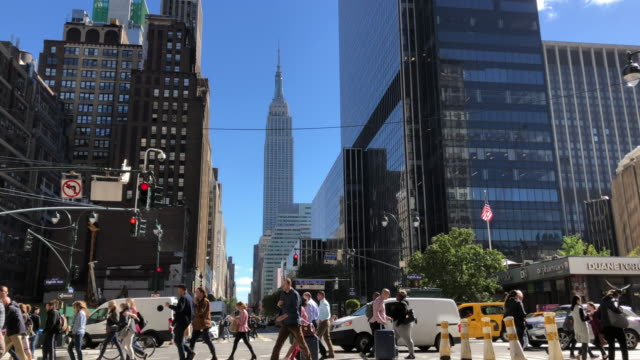 slow motion of people crossing street in new york city with empire state building in the background - manhattan stock-videos und b-roll-filmmaterial