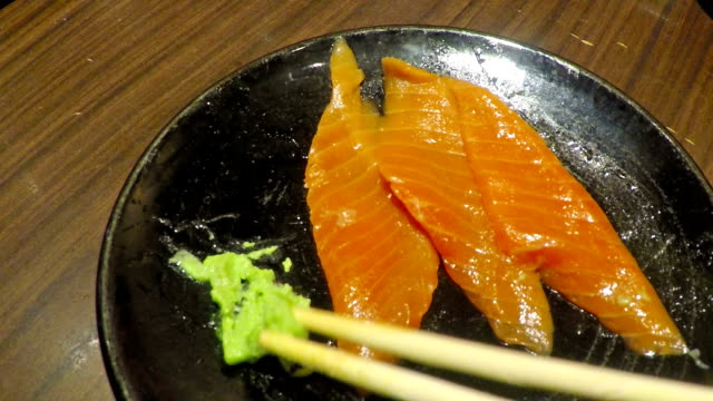 slow motion of people eating sashimi salmon and wasabi with chopsticks - wasabi stock videos and b-roll footage