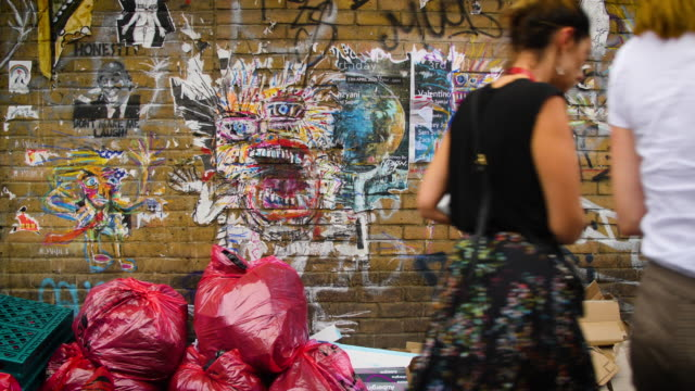slow motion of people passing in front of a brick wall with street art, graffiti and rubbish on brick lane, london - poster stock videos & royalty-free footage
