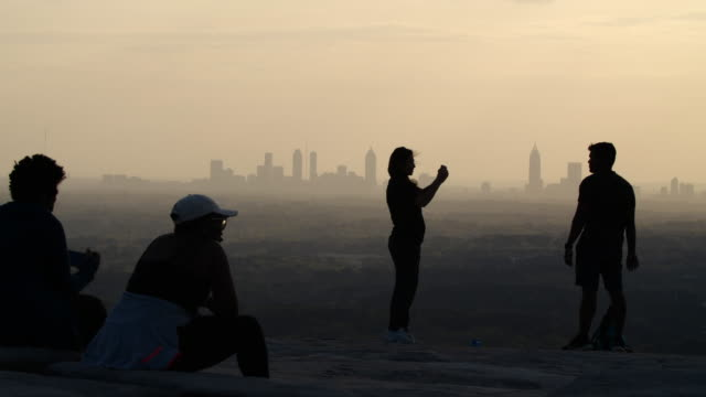 slow motion of people taking photo of the skyline at sunset - distant stock videos & royalty-free footage