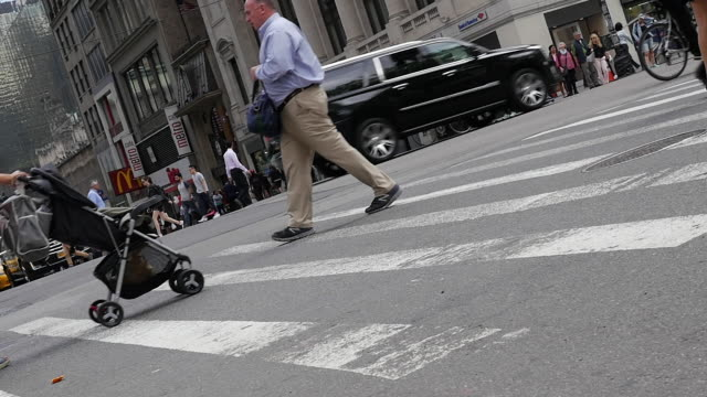 slow motion of people walking and crossing street in new york city - pushchair stock videos and b-roll footage