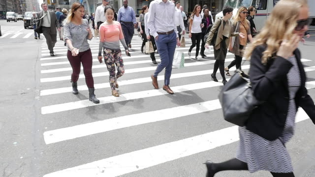 slow motion of people walking and crossing street in new york city - halbnahe einstellung stock-videos und b-roll-filmmaterial