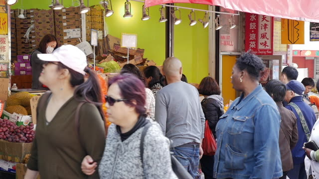 slow motion of people walking and shopping in flushing, queens, new york - 保護マスク点の映像素材/bロール