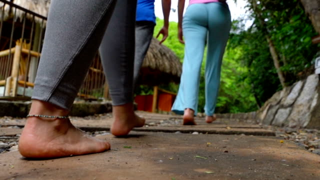 Slow motion of people walking barefoot to a yoga class outside