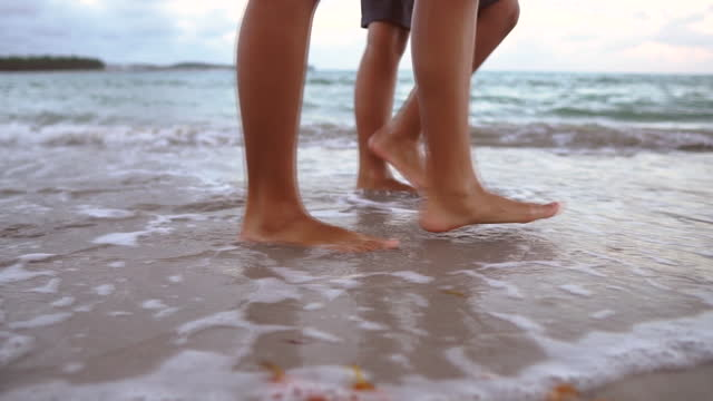 slow motion of people walking on the beach - barefoot stock videos & royalty-free footage