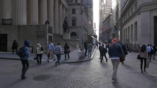 vídeos de stock, filmes e b-roll de slow motion of people walking on the wall street passing the federal hall - estátua