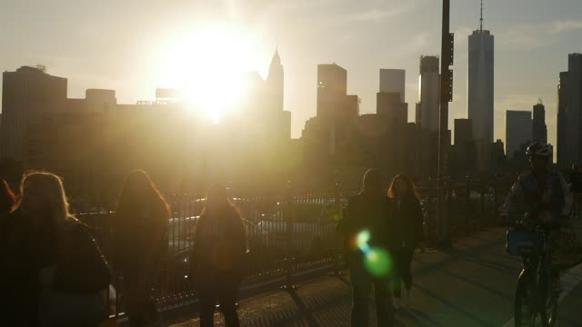 Slow motion of people walking on top of Brooklyn bridge at Sunset in New York City
