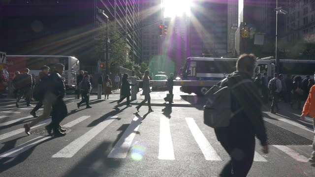 slow motion of people walking under bright sunlight at rush hour in the new york city - pedestrian crossing stock videos & royalty-free footage