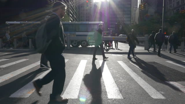 slow motion of people walking under bright sunlight at rush hour in the new york city - fußgänger stock-videos und b-roll-filmmaterial