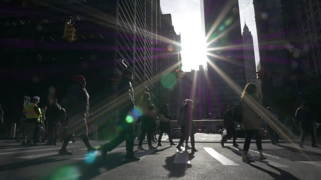 slow motion of people walking under bright sunlight at rush hour in the new york city - back lit woman stock videos & royalty-free footage