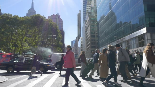 Slow motion of people walking with Empire state building in the background.