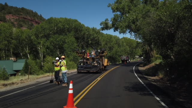 slow motion of people working at the new road construction in colorado, america amid the 2020 global coronavirus pandemic - construction vehicle stock videos & royalty-free footage