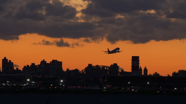 slow motion of plane taking off in laguardia airport at twilight and a flock of birds flying over, new york city - taking off stock videos & royalty-free footage