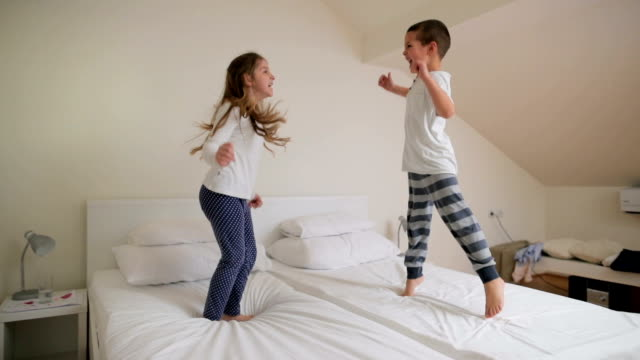 vídeos de stock e filmes b-roll de slow motion of playful children jumping on the bed and having fun. - cama