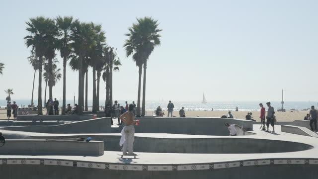 vídeos de stock, filmes e b-roll de slow motion of playground roller skating at venice beach - inclinação