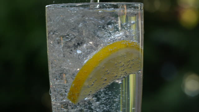 vídeos de stock e filmes b-roll de slow motion of pouring a glass of soda water with ice cubes and lemon - hd format