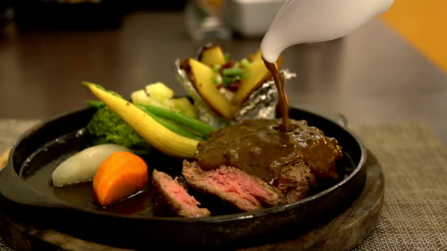 Slow motion of pouring black pepper sauce to beef steak