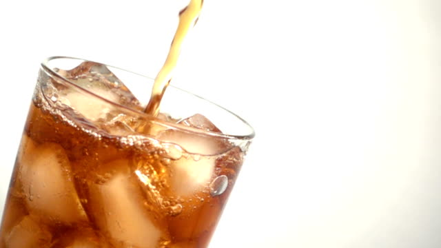 Slow motion of Pouring cola into the glass isolated on white background
