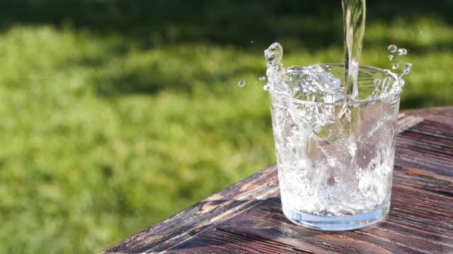 vidéos et rushes de mouvement lent de verser le verre d'eau - eau minérale