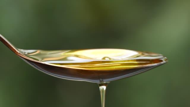 スプーンに油を注ぐスローモーション - オリーブ油点の映像素材/bロール