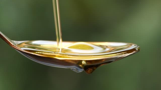 スプーンに油を注ぐスローモーション - オリーブ点の映像素材/bロール