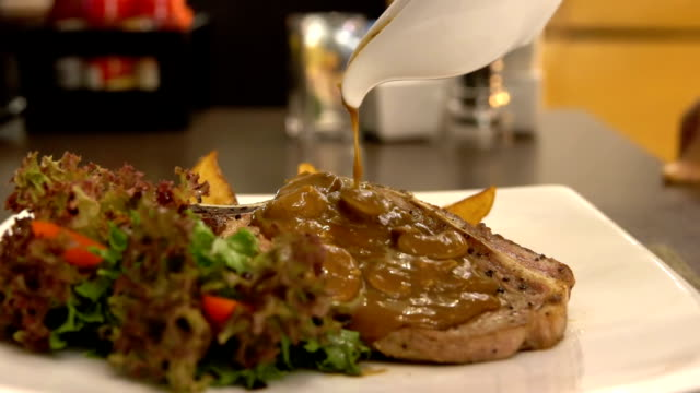 Slow motion of pouring pepper mushroom sauce to pork chop