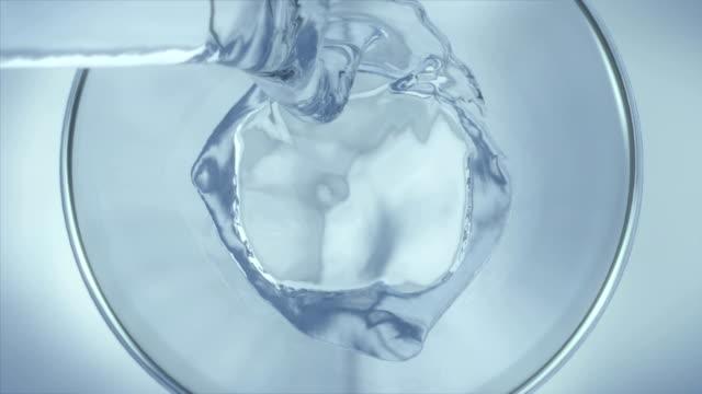vidéos et rushes de ralenti d'eau de coulée dans le verre, vue de dessus, close-up - verser