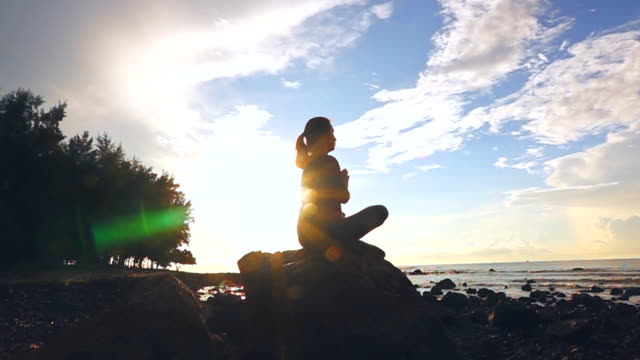 slow motion of practicing yoga on the beach at sunset - lotus position stock videos & royalty-free footage