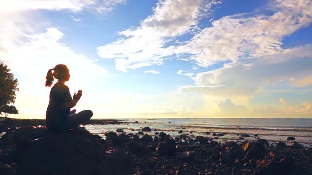 vídeos de stock e filmes b-roll de slow motion of practicing yoga on the beach at sunset - zen