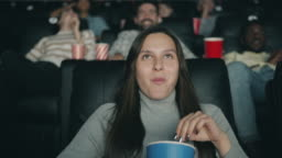 Slow motion of pretty brunette enjoying film in cinema laughing eating popcorn
