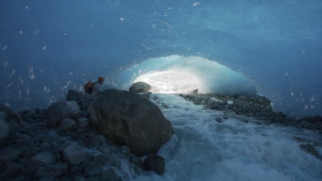 slow motion of raging river piercing through glacier ice cave in alaska - 地下点の映像素材/bロール