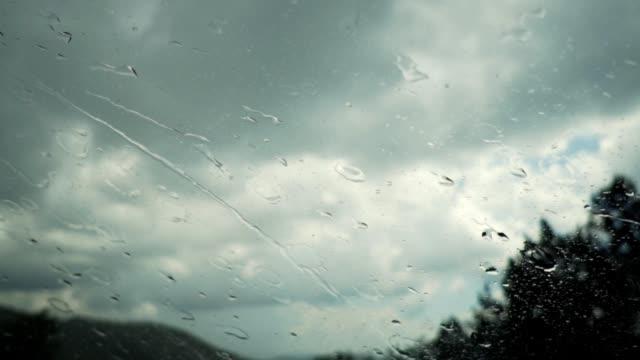 vídeos de stock e filmes b-roll de slow motion of rainy day view during car windshield wipers rain drops sliding down inside a car - escorregadio