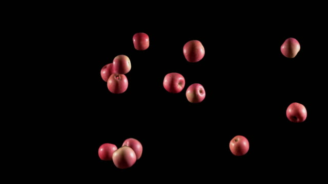 Slow motion of red apple being toss and thrown on black background