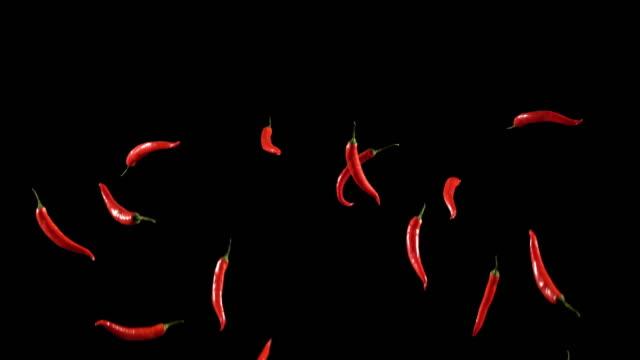 Slow Motion van rode Chili wordt gegooid en geworpen op zwarte achtergrond