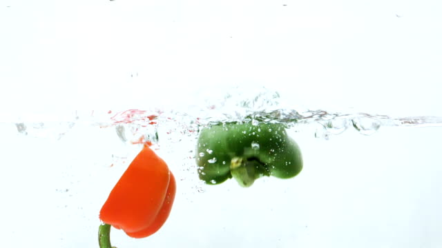 slow motion of red, green bell pepper drop in the water - green bell pepper stock videos & royalty-free footage
