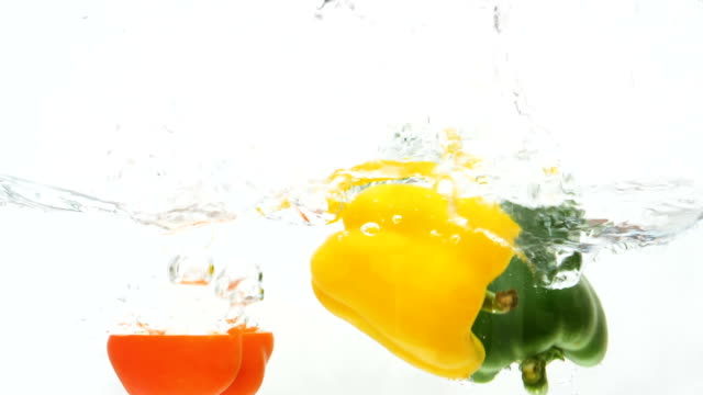 slow motion of red, green, yellow bell pepper drop in the water - still life stock videos and b-roll footage