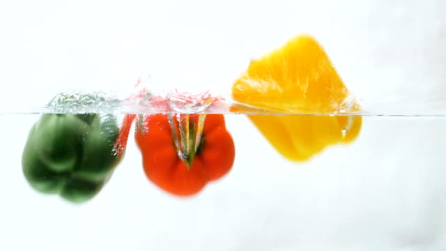slow motion of red, green, yellow bell pepper drop in the water - green bell pepper stock videos & royalty-free footage