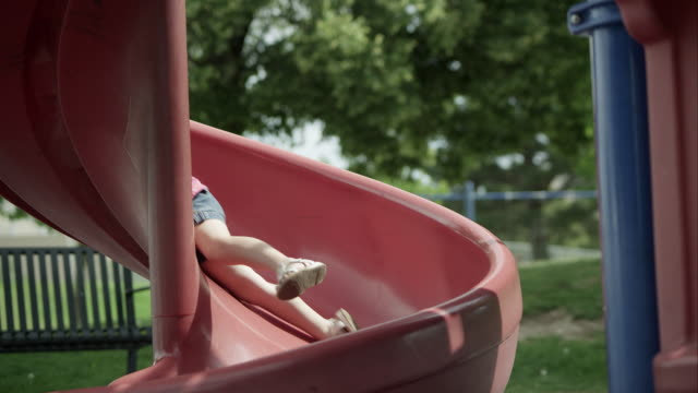 slow motion of red headed girl coming down slide and smiling. - rutschen stock-videos und b-roll-filmmaterial