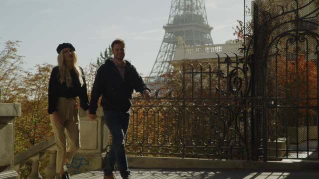 slow motion of romantic couple holding hands and walking near eiffel tower / paris, ile de france, france - eiffel tower paris stock videos & royalty-free footage