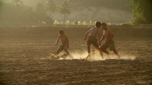 vídeos y material grabado en eventos de stock de lenta de los niños rurales están jugando fútbol en el día de sol en un pueblo. - países en vías de desarrollo