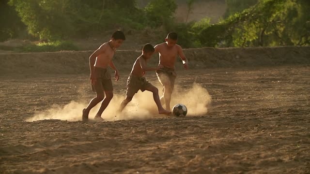 slow motion of rural children are playing football in the sunshine day in a village. - calcio sport video stock e b–roll